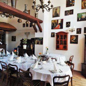 Wnętrze restauracji Anatewka: udekorowane stoły i obrazy na ścianach